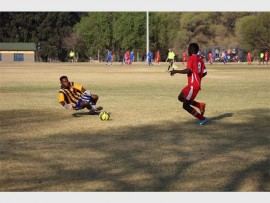 A Germiston City Football Club player (red) takes a shot at goal.