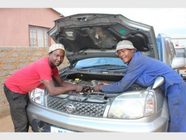 Mario Nyoni (left) is seen working on a client's vehicle with another mechanic, Matthews Tilo.