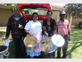 From left: Zolani Mgwaza, Paulina Mnguni, Bishop Nomvula Ximba and Humphrey Zondi of Uthando Lwenkosi Home-Based Care show their empty pots after having served lunch to needy learners at KwaThema.