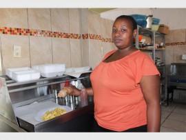 Kitchen manager Basetsana Mkhonza prepares a take-away plate for a customer.