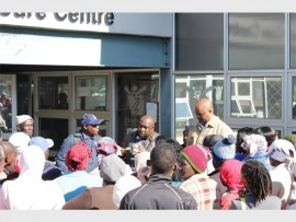Residents listen while ward councillor Wilson Busakwe (middle) address them regarding the blocked electricity.