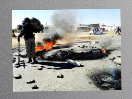 A metro police officer helping to clear Vlakfontein Road of burning tyres and rocks.