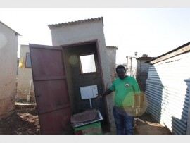 Community leader Kenneth Manana points out the lopsided toilet.