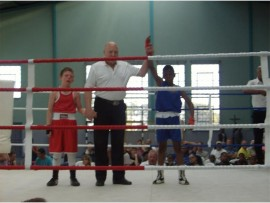 William Kleinhans stands in the ring with referee Charles Bench and local boxer Bongani Nzima.