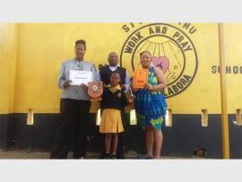 Class teacher Lindiwe Khoza (left) with school principal Vusi Gule and Grade Three teacher Kelebogile Ross show off the awards earned by learner Palesa Mnguni (front).