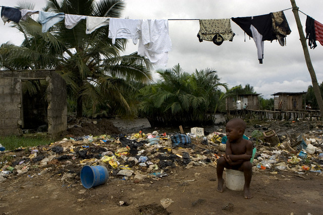 Young African boy surrounded by rubbish, going to the toilet on a bucket.