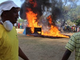 A protester walks by one of the many portable toilets that was set alight during the protest in Pretoria.