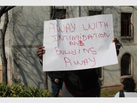 A protester at the Icasa offices holding up a sign that says,'Away with intimidation and bullying, away'.
