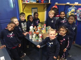 FasTracKids pupils with the tinned food they donated to charity for their annual food collection drive.