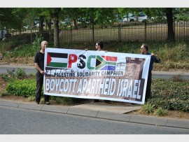 Protesters hold a banner to boycott apartheid Israel.