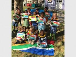 Preschoolers show off their handmade artwork on Heritage Day.