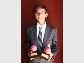 Shivenesen Muthan with his two awards for taking five wickets in two separate innings.