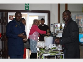 SOMETHING WARM: Staff from the Eden Park Library spent their 67 minutes for Mandela Day distributing cups of soup to patients at the Eden Park Clinic. Michael Sekomane (right) is the local librarian.