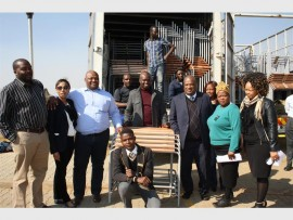 FURNITURE AT LAST: The principal of Palmridge Extention 6 Seconday School, Job Moshoeshoe (third from the right), accepts the tables and chairs from Giant Langman (third from the left) of Urban Dynamics. With them are councillor Robert Pienaar (middle) and Natishwa Jakalashe (right) of Human Settlements EMM.