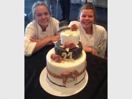 PIECE OF CAKE: Tamzin Geyser and Shay Delport with tteir baked creation, that ensured them second place in the Food and Beverage Cake Competition. *Photograph provided.