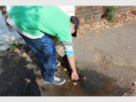 METER READING: A resident in Turffontein Street, Kenilworth trying to stop a leaking meter outside his yard.