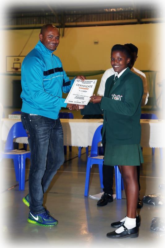 Nthabiseng Gumede receives her certificate for being selected for the KZN girls U15 soccer team from Bafana Bafana legend, Shaun Bartlett.