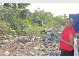 Zanele Mngadi surveys the mess the heavy rains last month caused in the Isipingo Transit Camp.