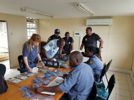 Police comb through the pirate DVDs seized in Isipingo CBD.