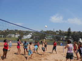 The learners play volleyball on the beach.