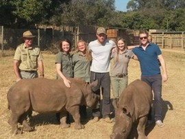 Prince Harry, wearing a cap, with staff from  Care for Wild Rehabilitation Centre.