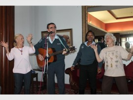 """Capt Peter Keogh serenades the residents at Edenroc Retirement Home after his crime awareness talk with""""shimmy girls"""" Shirley Geraghty, Const Mbali Bhengu and Yvonne Lee."""