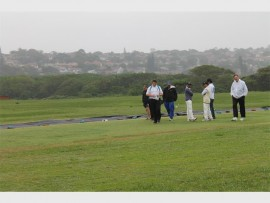 Dejected Quins and Dawn Heights cricket players with official umpires, in adverse weather conditions at Harlequins on Sunday morning.