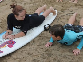 Instructor Claire Forbes teaching Nicole Schmidt how to surf.