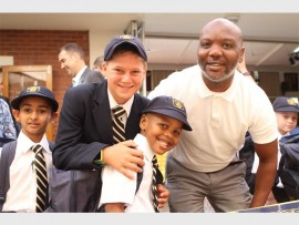 DPHS Grade 7 boy, Matt Wilson welcomes Grade 1 learners, Yunus Limalia and Mnotho Ngema and Mnotho's dad, Siphiwe, to the school.