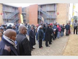 Joburg City Council officials and recipients of the Bothlabela Flats (behind) at the handover ceremony.