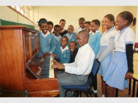 A DELIGHTED Hendrick Tema, a Grade 7 pupil of Iphutheng Primary School tries out a song on the donated piano with his excited music classmates watching on.