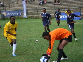 Hlompho Thite of MC Weiler gives cover to her goalkeeper Tiisetso Ngake as Iphutheng strikers (navy blue) advance.