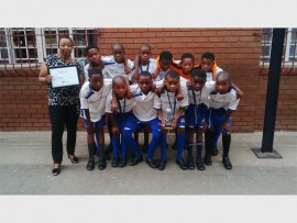 School teacher Thembeka Mpungose stands next to the Zenzeleni Primary School U12 soccer team members. Team captain, Knowledge Masuluke holds the 2016 Discovery Soccer Tournament's silver trophy.