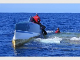 The NSRI Agulhas sea rescue team attaches a satellite tracking beacon to the upturned hull.