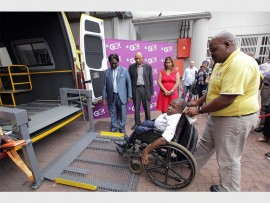 eThekwini Municipality Speaker, Cllr Logie Naidoo, together with ETA's Shoneeze Franks (in red) and Logan Moodley watch as driver Mfanafuthi Ngcobo and current Dial-A-Ride user, Sboniso Dlamini, demonstrate how the lift of one of the new GO!Durban Dial-A-Ride bus works.