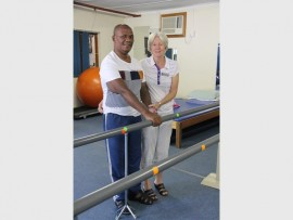 Myra Bagley, a physiotherapist at Headway-Natal with member, Johannes Madonsela, who had a stroke that left him wheelchair bound and he has since learnt to walk again.