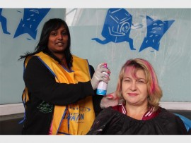 Cookie Govender sprays Annalize van den Berg's hair during the shavathon. PHOTO: Thobele Nzama