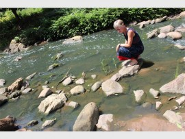 Westville resident, Sanet Beukes shows the polluted river water.
