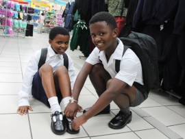 Tumelo Zondi. a Grade 4 pupil from KwaCutshwayo Primary School helps his little sister,  Nandi Zondi with her new school uniform.