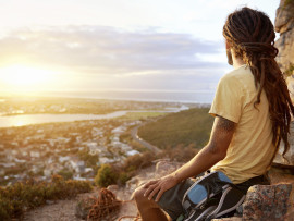 A man in dreadlocks on a mountain looking at the view with copyspace