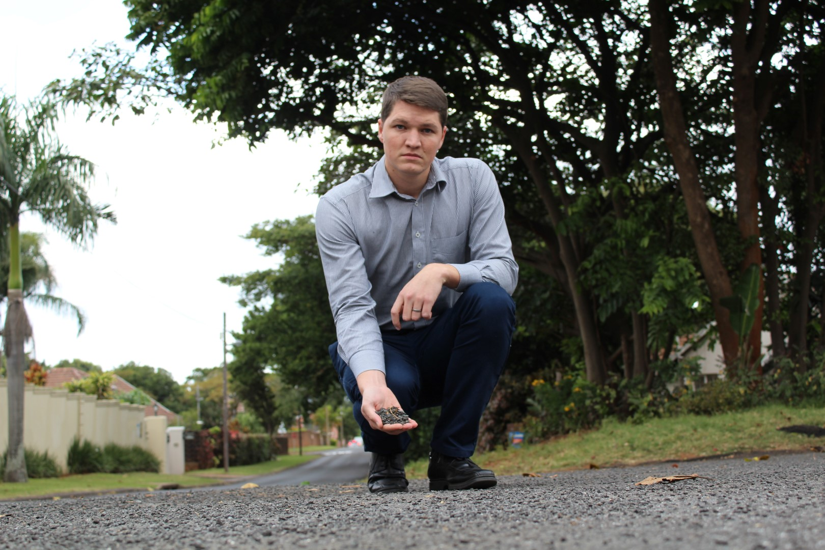 Durban North ward councillor, Shaun Ryley holds up some of the loose stones left behind in the recent resurfacing of several roads in north Durban.