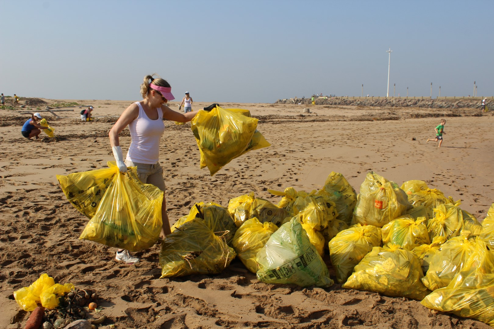 Liz Payne who regularly helps the monthly clean-ups puts some of the bags into a heap for collection.