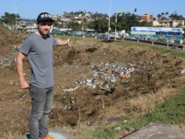Local resident, Jason Donnison, gestures to one of the spots hardest hit by illegal dumping at the intersection of Rinaldo Road and Chris Hani (North Coast) Road.