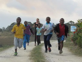Reaching out: Surielle Demming warming up for the Paddock Charity Run together with some  of the children at Rehoboth.