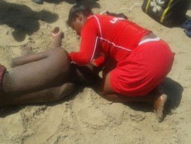 A 20-year-old man is treated by lifeguard  Musa Dlungwana after being swept out to sea at Port Edward's main beach yesterday. Pic: Zimasa Mgwili