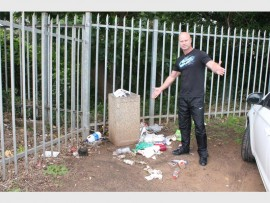 Mark Lawlor points to the overflowing bins in Connor Street, Port Shepstone.