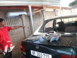 Anand Naidoo pointing out the damages on his car that was hacked by the violent gang in Northdale.