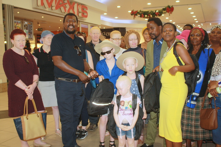 Chairperson of the Lenkosi Ngomane Project, Velankosini Ngidi, hands over school bags and stationary to beneficiaries during an albinism awareness programme at Boardwalk Inkwazi Shopping Centre last week