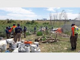 Metro police burn items found at an illegal squatter camp near Olifantsfontein Road in Midrand.