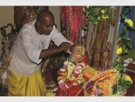 Rajendra Jaggernath puts a garland on Lord Ganesha's murthee.